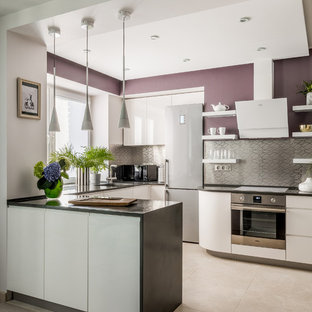 На фото: п-образные кухни в современном стиле с плоскими фасадами, белыми фасадами, фартуком цвета металлик, фартуком из металлической плитки, техникой из нержавеющей стали, полуостровом, бежевым полом и черной столешницей
