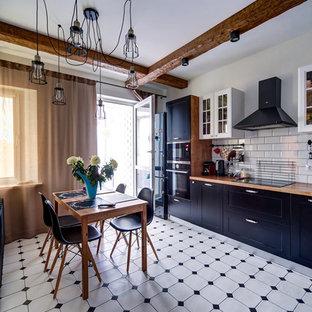 Выдающиеся фото от архитекторов и дизайнеров интерьера: отдельная кухня в стиле кантри с фасадами в стиле шейкер, черными фасадами, столешницей из дерева, белым фартуком, фартуком из плитки кабанчик, черной техникой и белым полом без острова