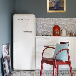Стильный дизайн: маленькая кухня в скандинавском стиле с фасадами с выступающей филенкой, белыми фасадами, серым фартуком, серым полом и белой столешницей без острова - последний тренд