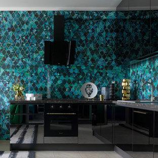 Aménagement d'une cuisine éclectique en L avec un évier posé, un placard à porte plane, des portes de placard noires, une crédence bleue, un sol beige et un électroménager noir.