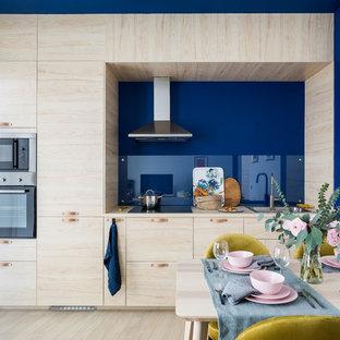 Idéer för små skandinaviska linjära kök med öppen planlösning, med en nedsänkt diskho, släta luckor, skåp i ljust trä, träbänkskiva, blått stänkskydd, glaspanel som stänkskydd, rostfria vitvaror och ljust trägolv
