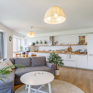 Inspiration for a scandinavian single-wall open plan kitchen in Other with a built-in sink, flat-panel cabinets, white cabinets, white splashback, metro tiled splashback and no island.