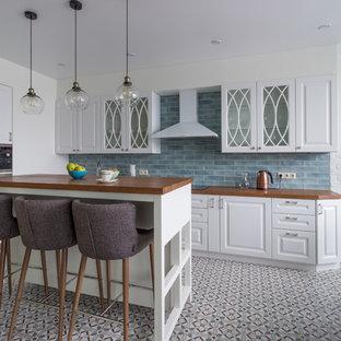 Идея дизайна: угловая кухня среднего размера в классическом стиле с белыми фасадами, деревянной столешницей, фартуком из керамической плитки, полом из керамической плитки, островом, обеденным столом, фасадами с выступающей филенкой, синим фартуком, разноцветным полом, коричневой столешницей и техникой из нержавеющей стали