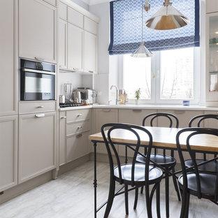 Свежая идея для дизайна: отдельная, угловая кухня в классическом стиле с накладной раковиной, фасадами с утопленной филенкой, серыми фасадами, белым фартуком, фартуком с окном и черной техникой без острова - отличное фото интерьера