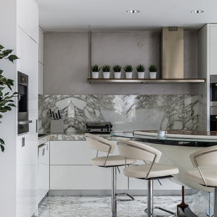 Photo of a contemporary l-shaped open plan kitchen in Other with a drop-in sink, flat-panel cabinets, white cabinets, marble benchtops, beige splashback, marble splashback, stainless steel appliances, marble floors, beige floor and beige benchtop.