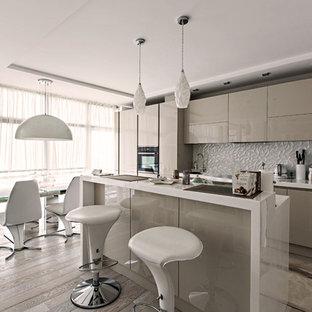 На фото: линейные кухни-гостиные среднего размера в современном стиле с плоскими фасадами, серыми фасадами, белым фартуком, черной техникой, островом, бежевым полом и белой столешницей