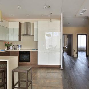 На фото: п-образная кухня в современном стиле с плоскими фасадами, белыми фасадами, бежевым фартуком, черной техникой, полуостровом, коричневым полом, белой столешницей и многоуровневым потолком с