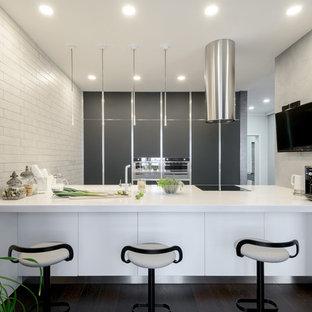 Свежая идея для дизайна: параллельная кухня-гостиная в современном стиле с плоскими фасадами, темным паркетным полом и островом - отличное фото интерьера