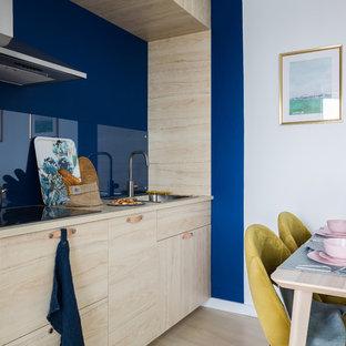 Неиссякаемый источник вдохновения для домашнего уюта: линейная кухня в современном стиле с обеденным столом, накладной раковиной, плоскими фасадами, синим фартуком, фартуком из стекла, бежевым полом и бежевой столешницей без острова