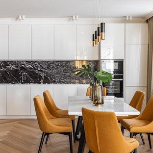 Свежая идея для дизайна: линейная кухня среднего размера в современном стиле с плоскими фасадами, белыми фасадами, черным фартуком, черной техникой, светлым паркетным полом, бежевым полом и черной столешницей - отличное фото интерьера