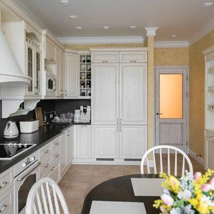 Пример оригинального дизайна: отдельная, угловая кухня в стиле современная классика с фасадами с выступающей филенкой, белыми фасадами, черным фартуком, белой техникой, бежевым полом и черной столешницей без острова
