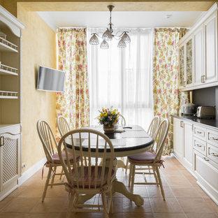 Свежая идея для дизайна: кухня в средиземноморском стиле с фасадами с выступающей филенкой, белыми фасадами, черным фартуком, белой техникой, бежевым полом и черной столешницей - отличное фото интерьера