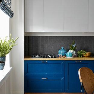 Новый формат декора квартиры: кухня в стиле современная классика с фасадами с утопленной филенкой, черным фартуком и синими фасадами