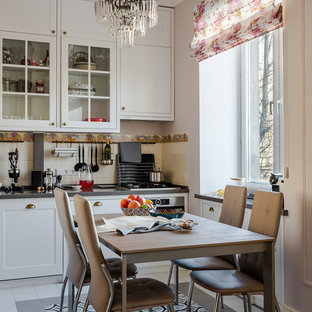 Inspiration for a small traditional single-wall eat-in kitchen in Moscow with glass-front cabinets, white cabinets, quartz benchtops, beige splashback, ceramic splashback, stainless steel appliances, ceramic floors, grey benchtop, no island and multi-coloured floor.