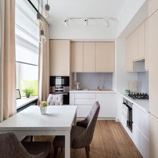 На фото: угловые кухни-гостиные в современном стиле с накладной раковиной, плоскими фасадами, серым фартуком и черной техникой без острова