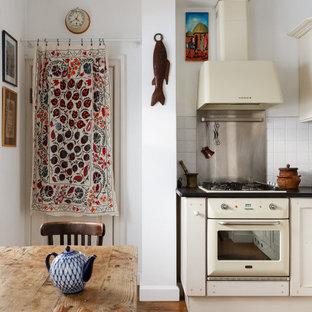 Свежая идея для дизайна: кухня в стиле кантри с плоскими фасадами, белыми фасадами, белым фартуком, фартуком из керамогранитной плитки, белой техникой, коричневым полом и черной столешницей без острова - отличное фото интерьера