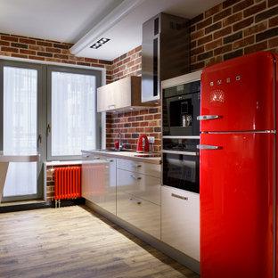 Modelo de cocina comedor lineal, industrial, con armarios con paneles lisos, puertas de armario blancas, encimeras beige, salpicadero de ladrillos, electrodomésticos de colores y suelo de madera clara