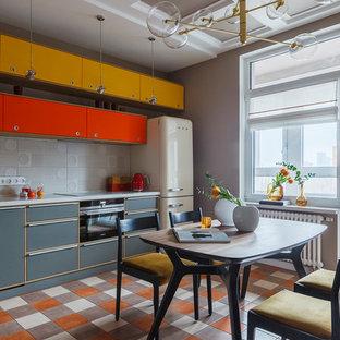 На фото: линейная кухня в стиле ретро с серым фартуком, разноцветным полом, обеденным столом, плоскими фасадами, серыми фасадами, цветной техникой и серой столешницей с