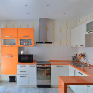 На фото: п-образная кухня среднего размера в современном стиле с накладной раковиной, плоскими фасадами, белыми фасадами, белым фартуком, техникой из нержавеющей стали, полуостровом, серым полом и оранжевой столешницей с