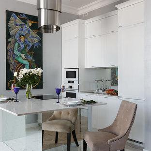 Идея дизайна: параллельная кухня-гостиная в стиле современная классика с врезной раковиной, белыми фасадами, белой техникой, островом, белым полом, белой столешницей, плоскими фасадами и фартуком из зеркальной плитки