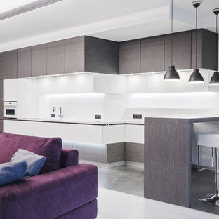 Photo of a large contemporary single-wall eat-in kitchen in Moscow with flat-panel cabinets, grey cabinets, white splashback, an undermount sink, solid surface benchtops, marble splashback, panelled appliances, porcelain floors and grey floor.