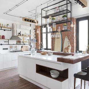 モスクワの大きいインダストリアルスタイルのおしゃれなキッチン (アンダーカウンターシンク、フラットパネル扉のキャビネット、白いキャビネット、木材カウンター、白いキッチンパネル、ガラス板のキッチンパネル、シルバーの調理設備の、クッションフロア、茶色い床) の写真