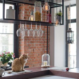 モスクワの中くらいのインダストリアルスタイルのおしゃれなキッチン (人工大理石カウンター、アンダーカウンターシンク、フラットパネル扉のキャビネット、白いキャビネット、レンガのキッチンパネル、パネルと同色の調理設備、クッションフロア、茶色い床) の写真