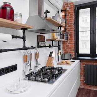 На фото: линейная кухня-гостиная среднего размера в стиле лофт с врезной раковиной, плоскими фасадами, белыми фасадами, столешницей из акрилового камня, белым фартуком, фартуком из стекла, техникой из нержавеющей стали, полом из ламината, островом и коричневым полом с
