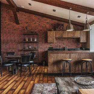 Идея дизайна: кухня в стиле лофт с плоскими фасадами, искусственно-состаренными фасадами, техникой из нержавеющей стали, паркетным полом среднего тона и полуостровом