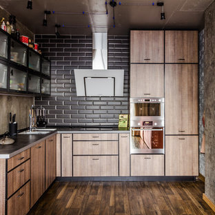 Photo of an industrial l-shaped open plan kitchen in Other with flat-panel cabinets, medium wood cabinets, black splashback, subway tile splashback, stainless steel appliances, dark hardwood floors, no island, brown floor, a double-bowl sink and stainless steel benchtops.
