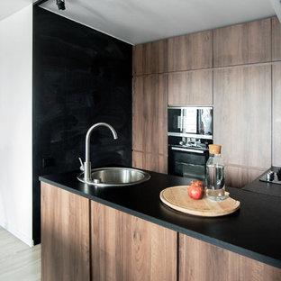 Создайте стильный интерьер: п-образная кухня в современном стиле с накладной раковиной, плоскими фасадами, фасадами цвета дерева среднего тона, черной техникой, полуостровом, черной столешницей и бежевым полом - последний тренд