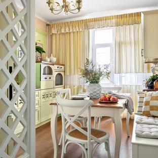 Неиссякаемый источник вдохновения для домашнего уюта: линейная кухня среднего размера в стиле шебби-шик с обеденным столом, фасадами с утопленной филенкой, зелеными фасадами, белой техникой, темным паркетным полом, коричневым полом и белой столешницей