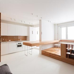 На фото: параллельная кухня в стиле модернизм с белым полом, плоскими фасадами, белыми фасадами, белой техникой, полуостровом и белой столешницей