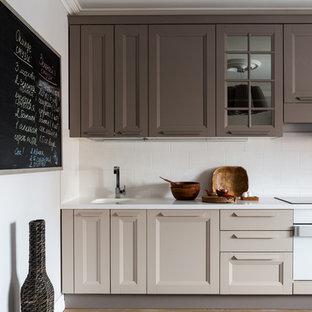 Пример оригинального дизайна: кухня в стиле современная классика с фасадами с утопленной филенкой, бежевыми фасадами, белым фартуком, коричневым полом и белой столешницей