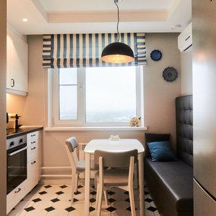 Идея дизайна: кухня в современном стиле с плоскими фасадами, техникой из нержавеющей стали, белым полом, черной столешницей и черно-белыми фасадами без острова