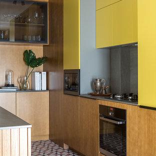 Неиссякаемый источник вдохновения для домашнего уюта: отдельная, параллельная кухня в современном стиле с плоскими фасадами, желтыми фасадами, серым фартуком, техникой из нержавеющей стали и разноцветным полом без острова