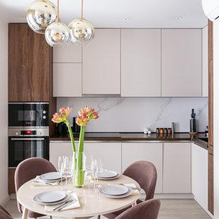 Стильный дизайн: угловая кухня среднего размера в современном стиле с обеденным столом, врезной раковиной, плоскими фасадами, бежевыми фасадами, белым фартуком, фартуком из керамогранитной плитки, техникой под мебельный фасад, бежевым полом и коричневой столешницей - последний тренд
