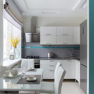 Свежая идея для дизайна: маленькая угловая кухня-гостиная в современном стиле с накладной раковиной, плоскими фасадами, белыми фасадами, серым фартуком, техникой из нержавеющей стали, белым полом и серой столешницей без острова - отличное фото интерьера