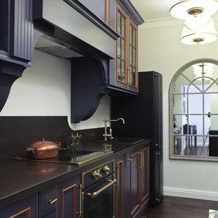 На фото: кухня в классическом стиле с накладной раковиной, черной техникой, темным паркетным полом, фасадами с декоративным кантом и синими фасадами с
