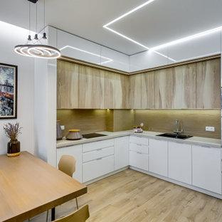 Стильный дизайн: угловая кухня среднего размера в современном стиле с обеденным столом, накладной раковиной, плоскими фасадами, белыми фасадами, бежевым фартуком, техникой из нержавеющей стали, бежевым полом и серой столешницей без острова - последний тренд
