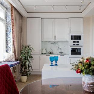 Свежая идея для дизайна: параллельная кухня в стиле современная классика с фасадами с выступающей филенкой, белыми фасадами, белым фартуком, белой техникой, паркетным полом среднего тона, полуостровом, коричневым полом, белой столешницей и многоуровневым потолком - отличное фото интерьера
