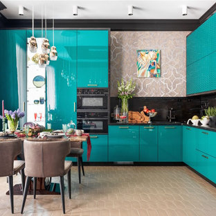 Новые идеи обустройства дома: угловая кухня-гостиная в стиле фьюжн с бирюзовыми фасадами, плоскими фасадами, черным фартуком, черной техникой, бежевым полом и черной столешницей без острова