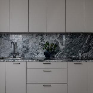 Idee per una cucina classica di medie dimensioni con lavello sottopiano, ante lisce, top in granito, paraspruzzi grigio, paraspruzzi in granito, elettrodomestici neri, pavimento in marmo, nessuna isola, pavimento grigio e top grigio