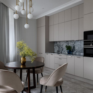 This is an example of a mid-sized contemporary single-wall eat-in kitchen in Moscow with an undermount sink, flat-panel cabinets, beige cabinets, granite benchtops, grey splashback, granite splashback, black appliances, marble floors, no island, grey floor and grey benchtop.