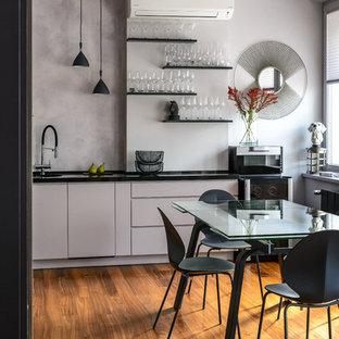 На фото: отдельная кухня в современном стиле с плоскими фасадами, серыми фасадами, серым фартуком, паркетным полом среднего тона, коричневым полом и черной столешницей с
