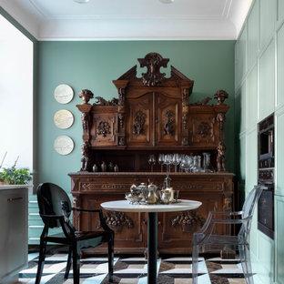 Cette image montre une cuisine américaine traditionnelle avec un placard avec porte à panneau encastré, des portes de placard turquoises, un électroménager en acier inoxydable, un sol multicolore et un plan de travail blanc.