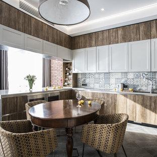На фото: п-образная кухня в современном стиле с двойной раковиной, плоскими фасадами, полуостровом, серым полом, обеденным столом, темными деревянными фасадами и разноцветным фартуком с