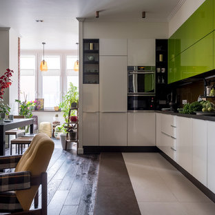 Mid-sized eclectic single-wall open plan kitchen in Moscow with a double-bowl sink, flat-panel cabinets, green cabinets, brown splashback, glass sheet splashback, stainless steel appliances, dark hardwood floors, brown floor and black benchtop.