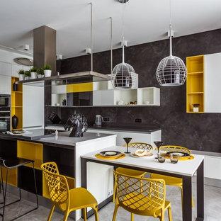 На фото: линейная кухня-гостиная в современном стиле с плоскими фасадами, белыми фасадами, серым фартуком, черной техникой, серым полом и островом с