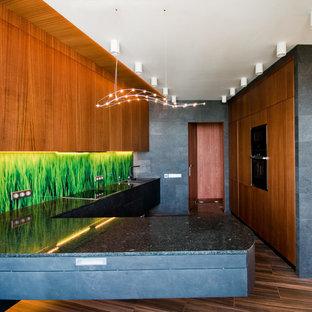 Идея дизайна: отдельная, п-образная кухня в современном стиле с накладной раковиной, плоскими фасадами, фасадами цвета дерева среднего тона, зеленым фартуком, полуостровом, коричневым полом, черной столешницей, техникой под мебельный фасад и темным паркетным полом